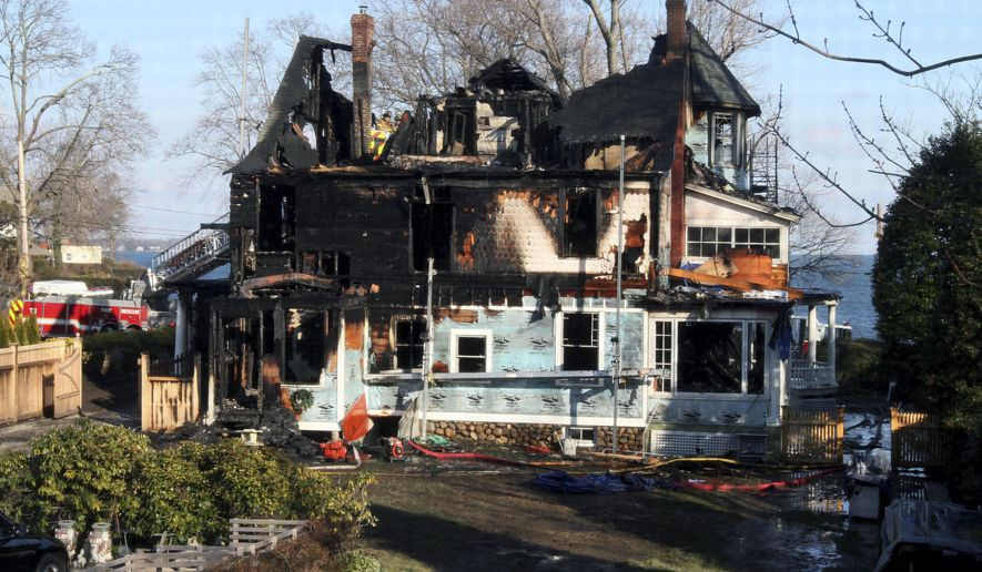 FILE - In this Dec. 25, 2011 file photo, firefighters investigate the home of Madonna Badger in Stamford, Conn., where a Christmas Day fire killed Badger's three daughters and both her parents. Court records obtained Tuesday, Jan. 13, 2015 by The Associated Press show that Michael Borcina and his contracting company settled a lawsuit by the children's father, Matthew Badger, in Hartford Superior Court by paying him $5 million. Madonna Badger and Borcina were dating at the time and both escaped the fire. Authorities said the fire began after Borcina left a bag of fireplace ashes in a bin in a mudroom in the house. ( AP Photo/Tina Fineberg, File)