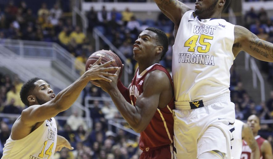 Oklahoma guard Buddy Hield (24) drives to the basket as West Virginia guard Gary Browne (14) and forward Elijah Macon (45) defend during the first half of an NCAA college basketball game, Tuesday, Jan. 13, 2015, in Morgantown, W.Va. (AP Photo/Raymond Thompson)