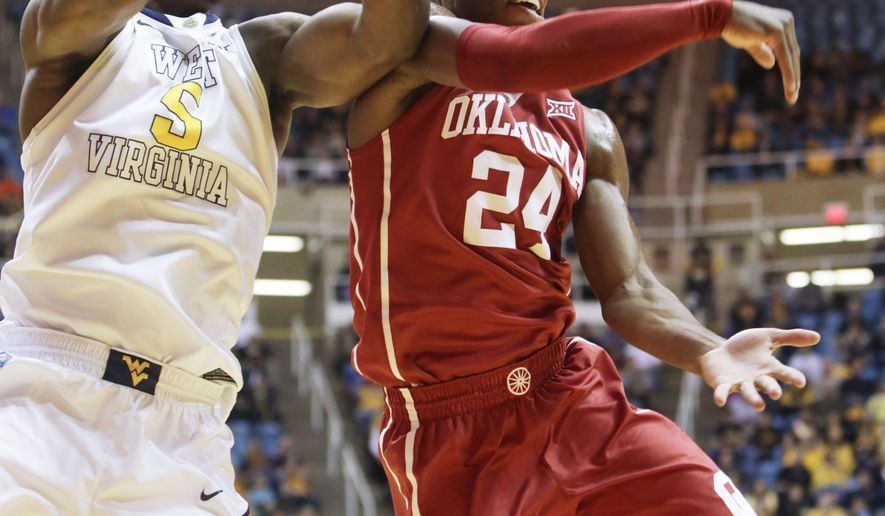 Oklahoma guard Buddy Hield (24) passes the ball to a teammate as West Virginia forward Devin Williams defends during the first half of an NCAA college basketball game, Tuesday, Jan. 13, 2015, in Morgantown, W.Va. (AP Photo/Raymond Thompson)
