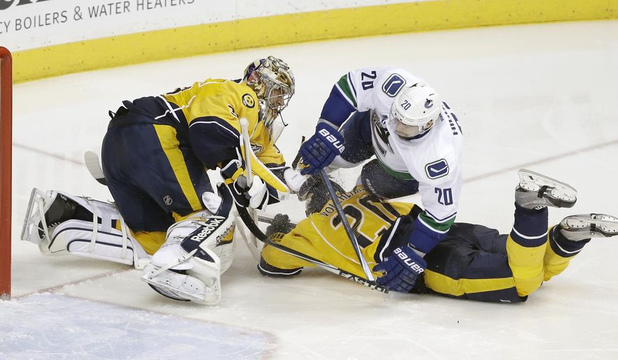 Nashville Predators goalie Pekka Rinne (35), of Finland, collides with defenseman Anton Volchenkov, of Russia, bottom right, and Vancouver Canucks left wing Chris Higgins, top right, in the third period of an NHL hockey game Tuesday, Jan. 13, 2015, in Nashville, Tenn. Rinne left the ice after the play. (AP Photo/Mark Humphrey)