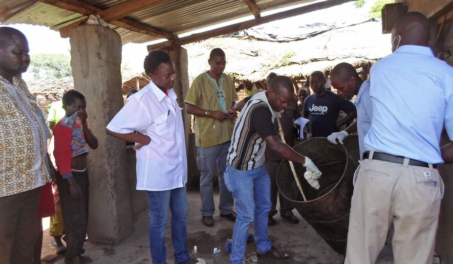 In this photo taken on Monday, Jan. 12, 2015, Mozambique government officials gather samples from a drum that was allegedly used to make local beer  that made people sick in Tete province, Mozambique.  Three more people have died from drinking contaminated beer, bringing the number of fatalities to 72, health authorities in Mozambique said on Tuesday. However, the number of victims hospitalized has decreased to 35 from 196, according Paula Bernardo, director of health, women and social welfare in the northeastern Tete province. (AP Photo/Antonio Chimundo)
