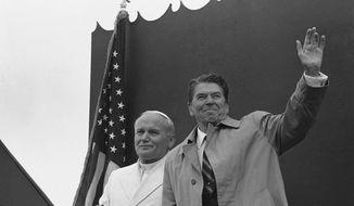 President Reagan with Pope John Paul II at his side, May 2, 1984. (AP Photo/Scott Stewart)