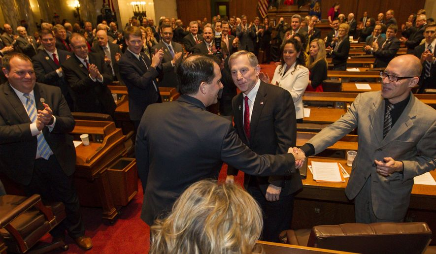 Wisconsin Gov. Scott Walker shakes hands with Rep. Scott Allen, right, R-Waukesha, before the Governor's State of the State address to a joint session of the Legislature in the Assembly chambers at the state Capitol Tuesday, Jan. 13, 2015, in Madison, Wis. (AP Photo/Andy Manis)
