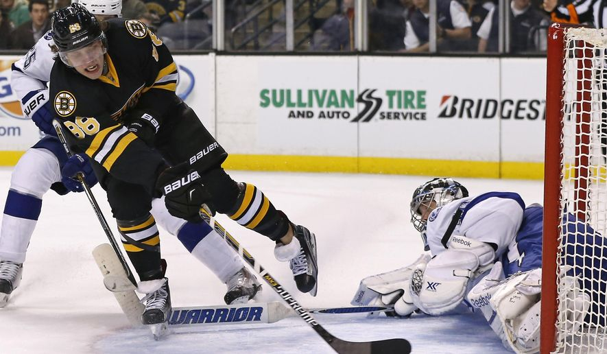 Boston Bruins left wing David Pastrnak (88) shoots in front of Tampa Bay Lightning defenseman Matt Carle, left, rear, and scores against goalie Ben Bishop during the second period of an NHL hockey game in Boston, Tuesday, Jan. 13, 2015. (AP Photo/Elise Amendola)