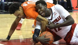 Louisville's Mango Mathiang, right, battles Virginia Tech's Shane Henry for a loose ball during the first half of their NCAA college basketball game Tuesday, Jan. 13, 2015 in Louisville, Ky. (AP Photo/Timothy D. Easley)
