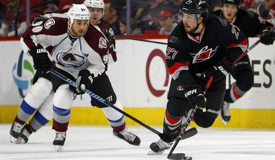 Carolina Hurricanes' Justin Faulk (27) looks to pass the puck in front of Colorado Avalanche's Ryan O'Reilly (90) during the first period of an NHL hockey game in Raleigh, N.C., Tuesday, Jan. 13, 2015. (AP Photo/Karl B DeBlaker)