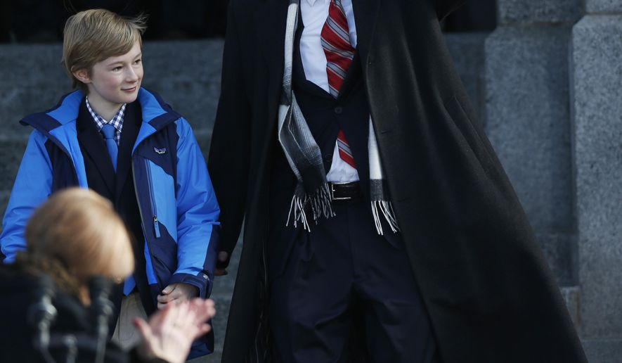 Flanked by his son, Teddy, Colorado Gov. John Hickenlooper waves to the crowd during his inauguration ceremony for a second term at the State Capitol, Tuesday, Jan. 13, 2015, in Denver. (AP Photo/David Zalubowski)