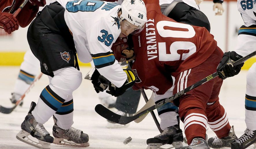 San Jose Sharks' Logan Couture (39) and Arizona Coyotes' Antoine Vermette (50) battle for the puck during the first period of an NHL hockey game Tuesday, Jan. 13, 2015, in Glendale, Ariz. (AP Photo/Ross D. Franklin)
