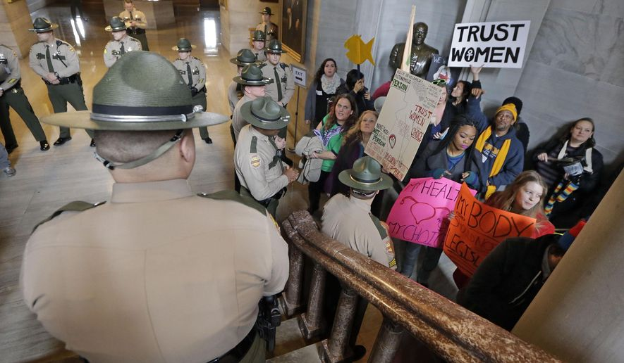 State troopers watch as abortion rights protesters protest in the Capitol on the opening day of the second session of the 109th General Assembly, Tuesday, Jan. 13, 2015, in Nashville, Tenn. (AP Photo/Mark Humphrey)