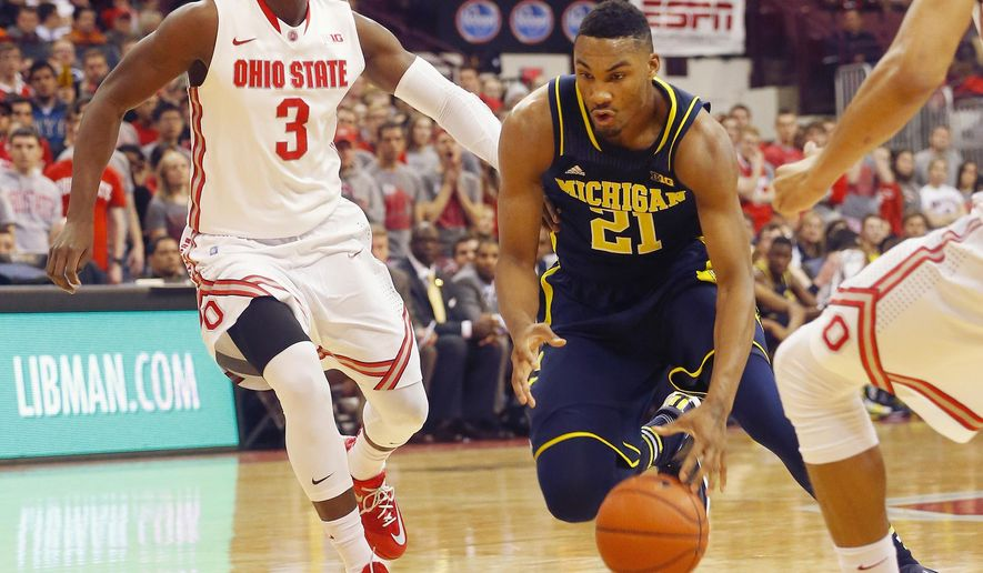 Michigan's Zak Irvin (21) drives past Ohio State's Shannon Scott (3) in the first half of an NCAA college basketball game, Tuesday, Jan. 13, 2015, in Columbus, Ohio. (AP Photo/Mike Munden)