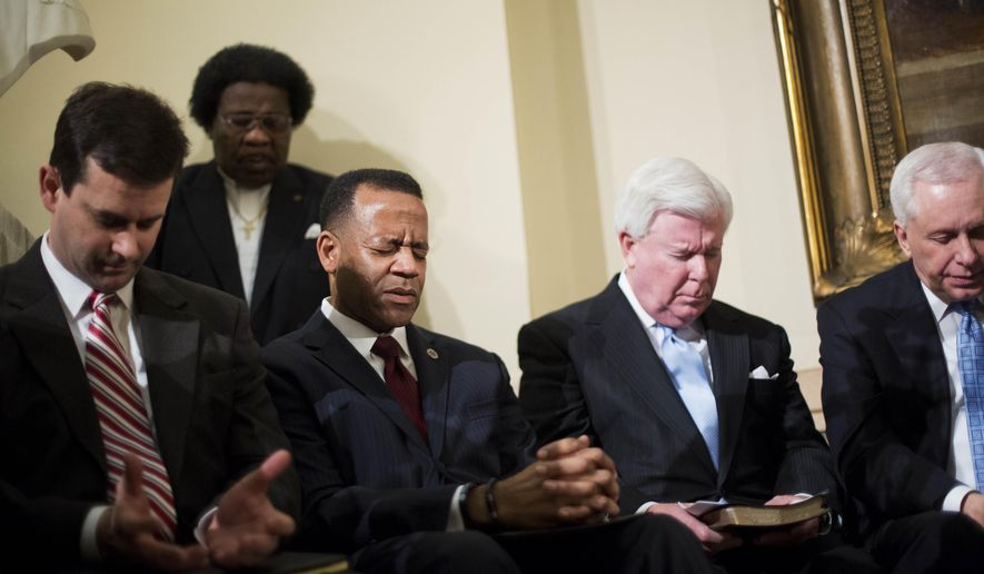 Former Atlanta fire chief Kelvin Cochran, third from right, observes a moment of prayer as religious groups rally to support him following his termination at the state Capitol, Tuesday, Jan. 13, 2015, in Atlanta. Mayor Kasim Reed says Cochran's termination was based on his judgment and not anti-gay statements in his self-published religious book. Reed suspended then fired Cochran after learning of his self-published book in which he described homosexuality as a perversion. Reed said in a statement Tuesday that an investigative report shows Cochran didn't have clearance to publish the book he gave to several subordinates at work. Cochran has said he did get approval from city officials to publish the book. (AP Photo/David Goldman)