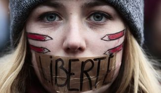 FILE – In this Sunday, Jan. 11, 2015, file photo, a woman with her mouth taped displaying the word Freedom, gathers with several thousand people in Berlin to honor the 17 victims who died during three days of bloodshed in Paris last week, and to support freedom of expression. (AP Photo/Markus Schreiber, File)