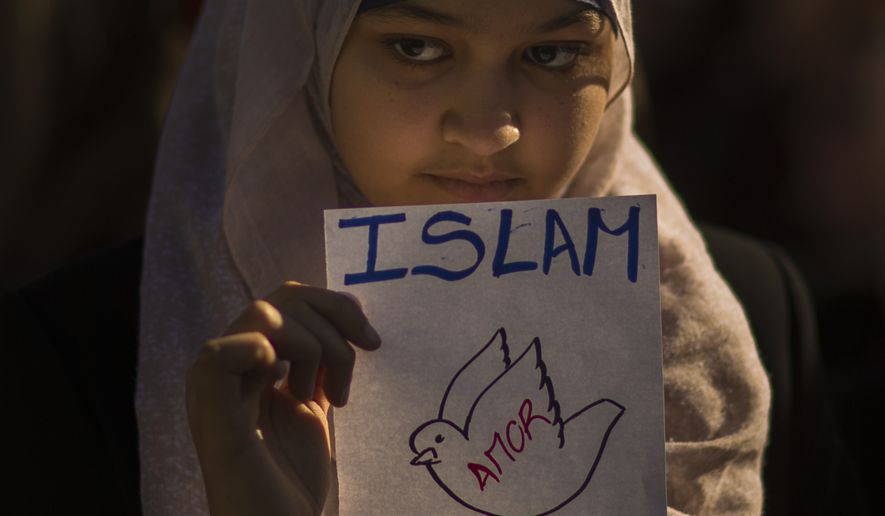 "In this Sunday, Jan. 11, 2015, file photo, a member of the Muslim community of Madrid holds a banner reading ""Islam is love"" during a gathering to honor the 17 victims, who died during three days of bloodshed in Paris. (Associated Press) **FILE**"