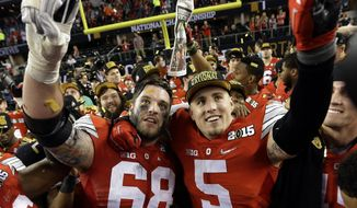 Ohio State's Taylor Decker (68) and Jeff Heuerman celebrate after the NCAA college football playoff championship game against Oregon Monday, Jan. 12, 2015, in Arlington, Texas. Ohio State won 42-20. (AP Photo/David J. Phillip)