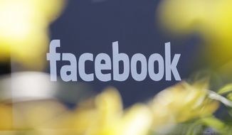 This Friday, May 18, 2012, file photo shows a sign at Facebook's headquarters behind flowers in Menlo Park, Calif. (AP Photo/Paul Sakuma, File)