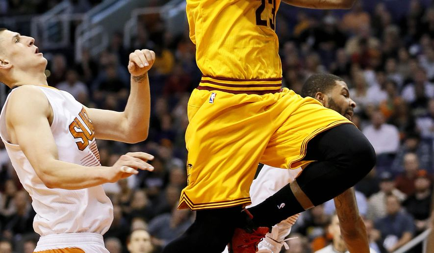 Cleveland Cavaliers' LeBron James (23) drives against Phoenix Suns' Alex Len during the first half of an NBA basketball game, Tuesday, Jan. 13, 2015, in Phoenix. (AP Photo/Matt York)