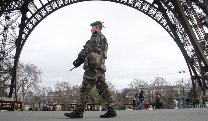 A French army soldier patrols under the Eiffel Tower in Paris, Tuesday Jan. 13, 2015. France on Monday ordered 10,000 troops into the streets to protect sensitive sites after three days of bloodshed and terror, amid the hunt for accomplices to the attacks that left 17 people and the three gunmen dead. (AP Photo/Remy de la Mauviniere)