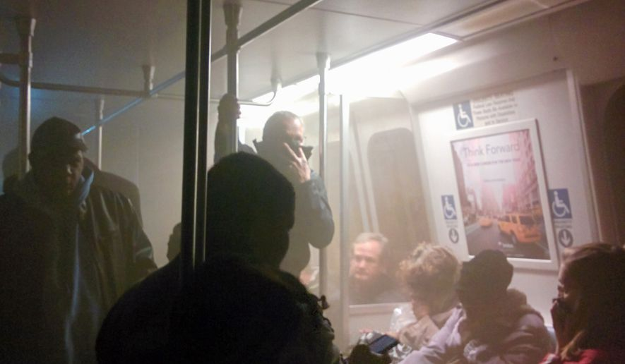Smoke fills a Washington Metro system subway car near the L'Enfant Plaza station in Washington, Monday, Jan. 12, 2015. The transit network in the nation's capital remained hobbled Tuesday morning after an electrical malfunction that filled the busy subway station with smoke, killing one woman and sending dozens of people to hospitals. (AP Photo/Andrew Litwin)