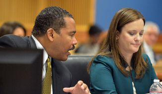 Dexter Scott King talks with attorney Nicole Wade during a hearing over who owns the Rev. Martin Luther King Jr.'s 1964 Nobel Peace Prize medal and traveling Bible on Tuesday, Jan. 13, 2015, in Fulton County Superior Court in Atlanta. (AP Photo/Atlanta Journal-Constitution, Kent D. Johnson)
