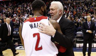 Washington Wizards guard John Wall (2) talks with San Antonio Spurs coach Gregg Popovich after an NBA basketball game, Tuesday, Jan. 13, 2015, in Washington. The Wizards won 101-93. (AP Photo/Alex Brandon)