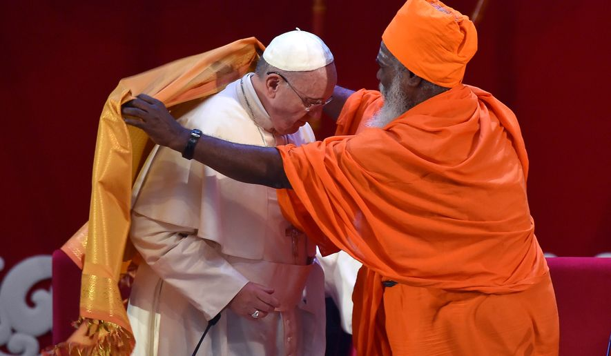 Pope Francis receives a saffron-colored robe from Hindu Kurukkal SivaSri T. Mahadeva during a meeting of representatives of the major faiths on the island at Bandaranaike Memorial International center in Colombo, Sri Lanka, Tuesday, Jan. 13, 2015. (AP Photo/Ettore Ferrari, pool)