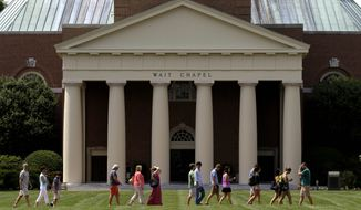A group walks across the lawn on the campus of Wake Forest University in Winston-Salem, N.C. (Associated Press)
