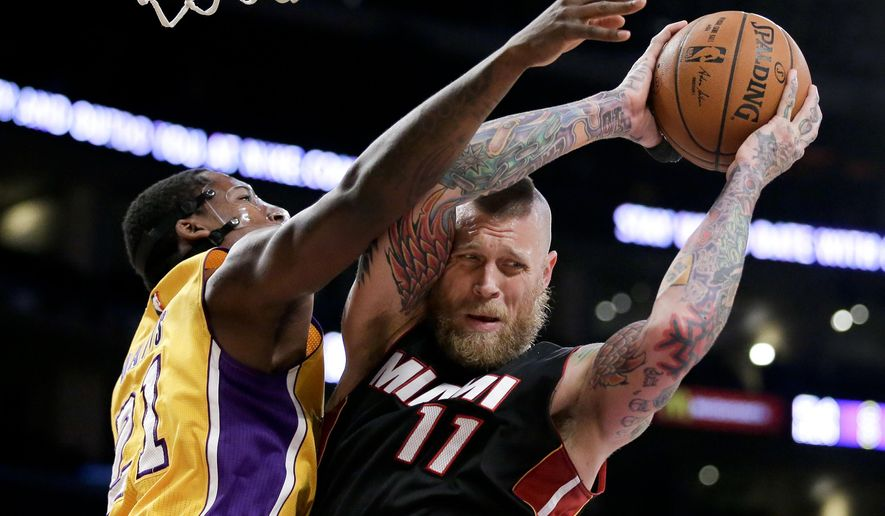 Miami Heat forward Chris Andersen, right, takes a rebound away from Los Angeles Lakers forward Ed Davis during the first half of an NBA basketball game in Los Angeles, Tuesday, Jan. 13, 2015. (AP Photo/Chris Carlson)