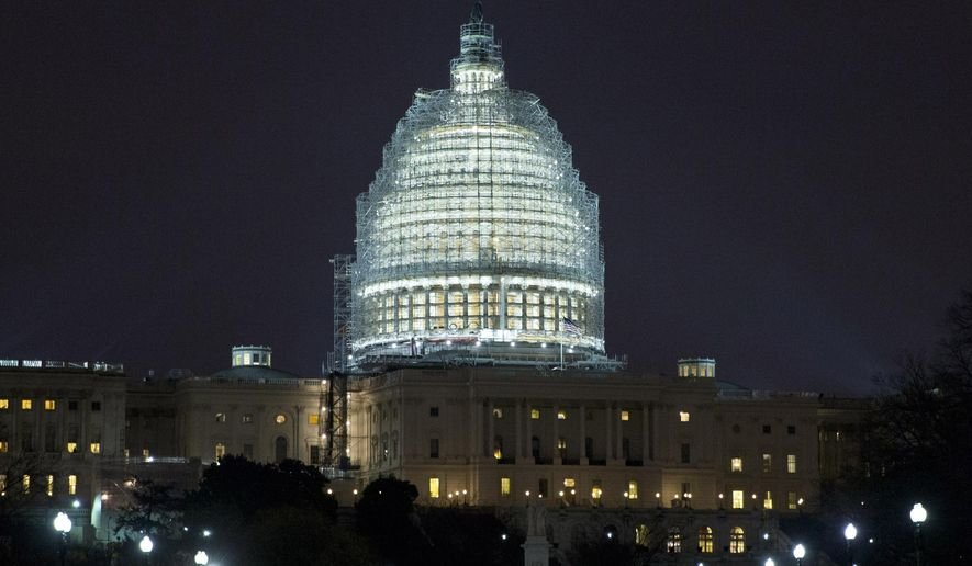 Lights illuminate the U.S. Capitol, which is covered in scaffolding for restoration, in Washington on Wednesday, Jan. 14, 2015. A man who plotted to attack the Capitol and kill government officials inside it and spoke of his desire to support the Islamic State militant group was arrested on Wednesday, the FBI said. (AP Photo/Jacquelyn Martin)