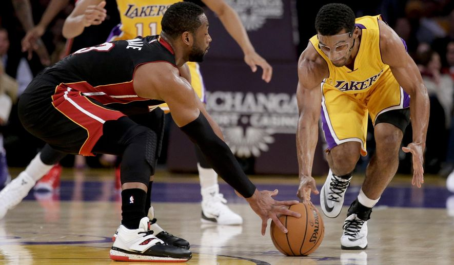 Los Angeles Lakers guard Ronnie Price, right, and Miami Heat guard Dwyane Wade reach for a loose ball during the first half of an NBA basketball game in Los Angeles, Tuesday, Jan. 13, 2015. (AP Photo/Chris Carlson)
