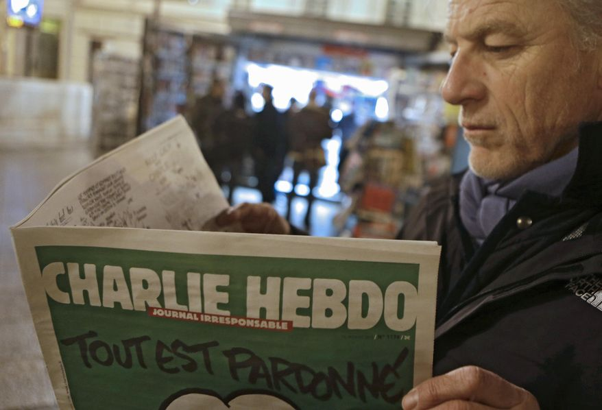 Jean Paul Bierlein reads the latest issue of Charlie Hebdo outside a newsstand in Nice, southeastern France, Wednesday, Jan. 14, 2015. (AP Photo/Lionel Cironneau)