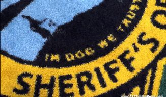 "This image released by ABC Action News, shows the Pinellas County Sheriff's Office rug in Largo, Fla., Wednesday, Jan. 14, 2015. WFTS news reported that the new rugs at the sheriff's administration building say ""In Dog We Trust"" instead of ""In God We Trust."" (AP Photo/WFTS-TV/ABC Action News, Adam Winer)"