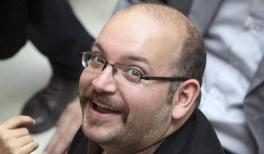 Jason Rezaian, an Iranian-American correspondent for The Washington Post, smiles as he attends a presidential campaign of President Hassan Rouhani in Tehran on April 11, 2013. The reporter has been detained in Iran for more than four months and was formally charged Dec. 6, 2014, after a daylong proceeding in a Tehran courtroom, the newspaper reported. (Associated Press) **FILE**
