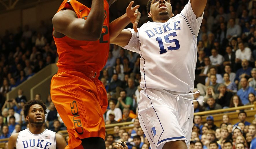CORRECTS YEAR - Duke's Jahil Okafor (15) goes to the basket against Miami's Deandre Burnett, left, as Duke's Justise Winslow (12) looks on during the first half of an NCAA college basketball game Tuesday, Jan. 13, 2015, in Durham, N.C. (AP Photo/Ellen Ozier)