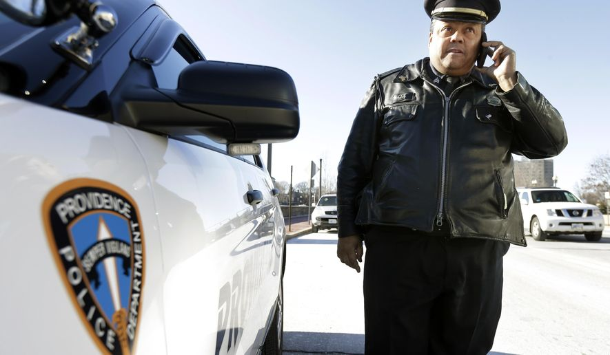 In this Tuesday, Jan. 13, 2015 photo, Rhode Island state Rep. Raymond Hull, D-Providence, also a Providence police sergeant, speaks on a mobile phone near his cruiser, in Providence, R.I. Hull says there are privacy issues that would need to be solved before passing a bill to require police to wear body cameras. (AP Photo/Steven Senne)