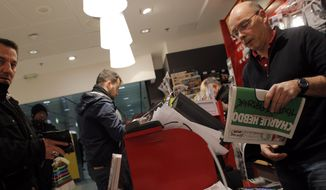 People queue up to buy Charlie Hebdo newspapers at a newsstand in Paris Wednesday, Jan. 14, 2015. In an emotional act of defiance, Charlie Hebdo resurrected its irreverent and often provocative newspaper, featuring a caricature of the Prophet Muhammad on the cover that drew immediate criticism and threats of more violence. (AP Photo/Christophe Ena)