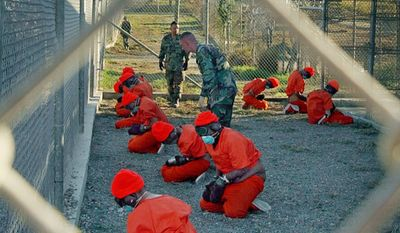 Taliban and al Qaeda detainees sit in a holding at Camp X-Ray at Naval Base Guantanamo Bay, Cuba, in this Jan. 11, 2002 photo. (Associated Press) ** FILE **