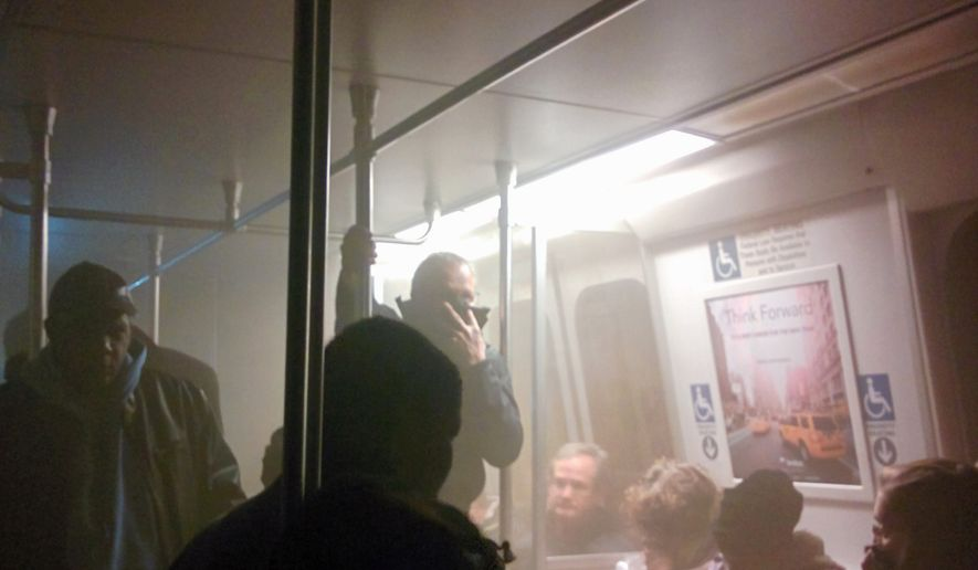 Smoke fills a Washington Metro system subway car near the L'Enfant Plaza station in Washington on Monday, Jan. 12, 2015. (AP Photo/Andrew Litwin)