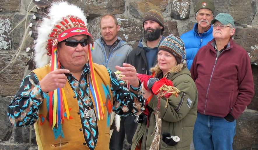 In a Monday, Jan. 12 2015 photo, Jimmy St. Goddard, left, a spiritual chief for the Blackfeet Tribe, talks as individuals involved in wolf reintroduction and management listen behind him, at Roosevelt Arch near Gardiner, Mt. It was 1995 when the first eight wolves live-trapped in Canada were placed inside fenced enclosures in Yellowstone to acclimate them to the area in hopes they would not immediately bolt back to their homeland. Twenty years later, about 130 wolves in 11 packs inhabit Yellowstone. From left to right are Dan Stahler, Yellowstone biologist; Nathan Varley, former field biologist volunteer; Doug Smith, Wolf Project biologist; and John Varley, former Yellowstone Resource Center chief.(AP Photo/The Billings Gazette, Brett French)