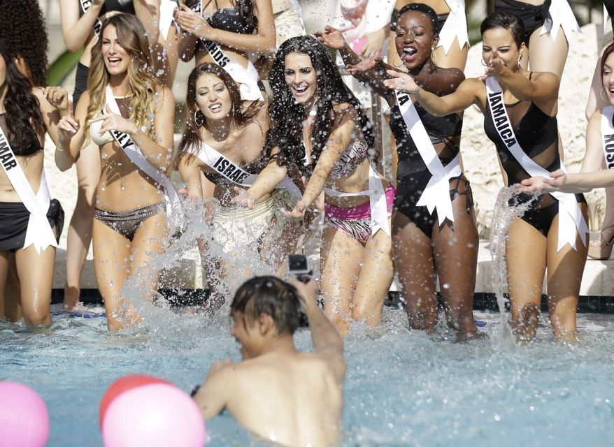 Miss Universe contestants Valentina Bonariva, of Italy, left, Doron Matalon, of Israel, Marcela Chmielowska, of Poland, Gaylyne Ayugi, of Kenya, and Kaci Fennell, of Jamaica, splash water at a photographer during the Yamamay swimsuit runway show, Wednesday, Jan. 14, 2015, in Doral, Fla. The Miss Universe pageant will be held Jan. 25 in Miami. (AP Photo/Lynne Sladky)
