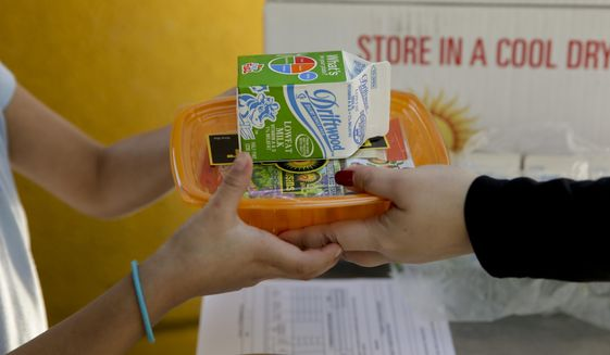 A student receives her afternoon snack at Kingsley Elementary School, Tuesday, Jan. 13, 2015, in Los Angeles. Many of the students at the school in a low-income neighborhood of Los Angeles eat breakfast and lunch provided by the school. (AP Photo/Jae C. Hong) ** FILE **