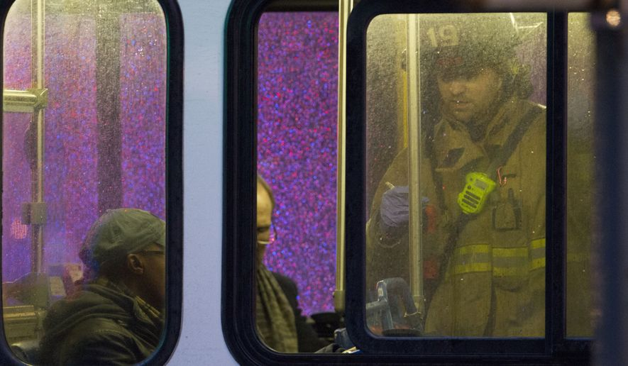 FILE - In this Jan. 12, 2015 file photo, a firefighter attends people on a bus to assess triage needs after people were evacuated from a smoke filled Metro subway tunnel in Washington. Passengers on a smoke-filled subway train in the nation's capital were still asking when help would arrive 27 minutes after the smoke was first reported, District of Columbia officials said Thursday. One woman died and dozens more were sickened when the train filled with smoke Monday afternoon near a busy station in downtown Washington. The cause of the electrical malfunction that led to the smoke remains under investigation.  (AP Photo/Jacquelyn Martin, File)