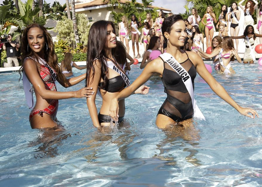 Miss Universe contestants Laurien Angelista, of Curacao, left, Yasmin Verheijen, of the Netherlands, and Kaci Fennell, of Jamaica, walk in the pool during the Yamamay swimsuit runway show, Wednesday, Jan. 14, 2015, in Doral, Fla. The Miss Universe pageant will be held Jan. 25 in Miami. (AP Photo/Lynne Sladky)