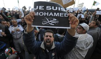 "A demonstrator holds up a ""Je suis Mohamed"" sign during a protest in Algiers, Algeria, Friday, Jan. 16, 2015. Algerian police are struggling to contain more than a thousand protesters thronging the streets of the capital denouncing cartoons of the Prophet Muhammad published by French satirical weekly Charlie Hebdo. Chanting ""I am not Charlie, I am Muhammad,"" protesters left their mosques after Friday prayers and gathered in downtown Algiers' May 1 square where they were met by hundreds of riot police. (AP Photo/Sidali Djarboub)"