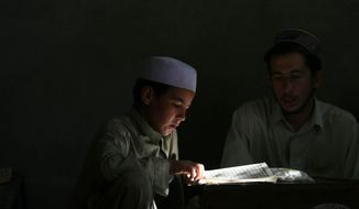 An Afghan boy reads the Koran in a madrasa or Islamic school in Kabul, Afghanistan. (AP Photo/Rafiq Maqbool)
