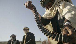 FILE - In this Dec. 28, 2011 file photo, a former Taliban fighter places a range of bullets before surrendering it to Afghan authorities, as part of a peace-reconciliation program in Herat, west of Kabul, Afghanistan. The Islamic State group controls a third of both Syria and Iraq, where it declared a caliphate governed by an extremely harsh interpretation of Shariah law and demanded the allegiance of the world's Muslims. The Taliban, by contrast, are narrowly focused on Afghanistan and Pakistan, and some leaders have even responded to past peace overtures. (AP Photo/Reza Shirmohammadi, File)
