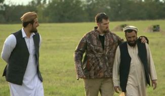 """Mohammed Gulab walks with former Navy SEAL Marcus Luttrell during a 2013 interview in the United States. (Image: CBS, """"60 Minutes"""" screen shot)"""