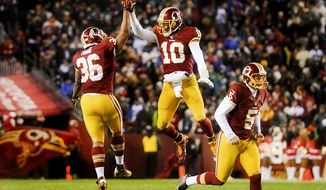 Washington Redskins fullback Darryl Young (36), left, celebrates with Washington Redskins quarterback Robert Griffin III (10) after scoring on a 1 yard run at the end of the third quarter as the Washington Redskins play the Philadelphia Eagles at FedEx Field, Landover, Md., Saturday, December 20, 2014.