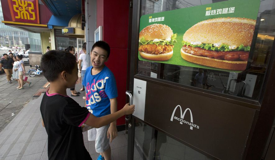 FILE - In this July 31, 2014, file photo, boys open the door to a McDonald's restaurant in Beijing. Long a symbol of American economic might, the rising dollar is denting the earnings of U.S. companies that operate overseas. (AP Photo/Ng Han Guan, File)