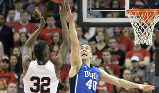 Duke's Marshall Plumlee, right, attempts to block a shot by Louisville's Chinanu Onuaku during the first half of an NCAA college basketball game, Saturday, Jan. 17, 2015, in Louisville, Ky. (AP Photo/Timothy D. Easley)
