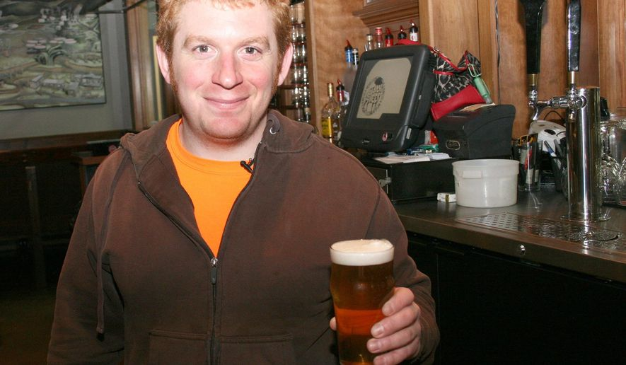 ADVANCED FOR RELEASE SATURDAY, JANUARY 17, 2015 Ryan Heastings, head brewer at Black Sheep Burrito and Brews, poses for a photo holding one of several brews on tap in Charleston, W.Va., Jan. 11, 2015. (AP Photo/Charleston Daily Mail, Billy Wolfe)